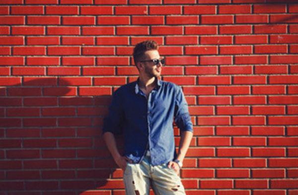 Харизматичный парень в солнцезащитных очках на фоне красной кирпичной стены