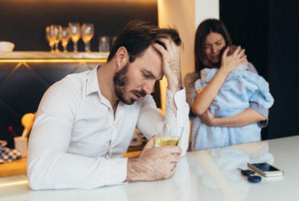 Мужчина со стакан спиртного. На заднем плане женщина с грудничком на руках, у нее слезы на глазах