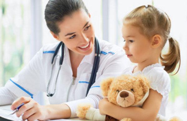 Девочка с плюшевым медведем в руках разговаривает с доктором