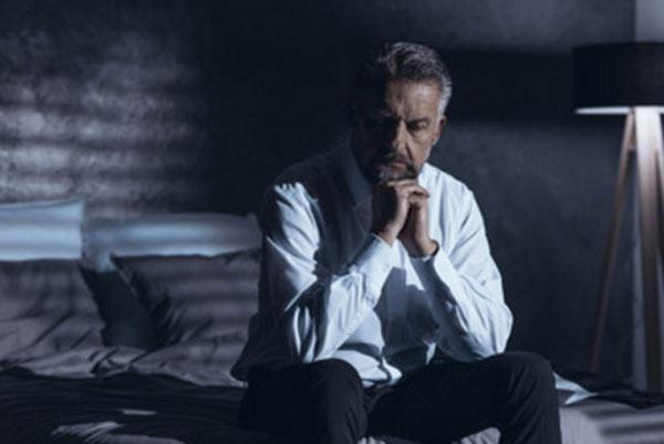 Седой мужчина сидит в задумчивости на кровати