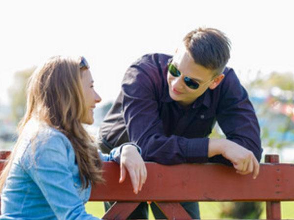 Парень флиртует с девушкой, которая сидит на скамейке