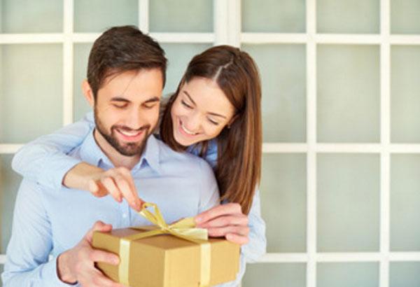 Женщина стоит за спиной мужчины и помогает ему открыть коробку с подарком