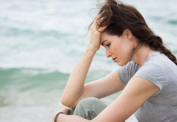 Расстроенная девушка сидит на берегу моря