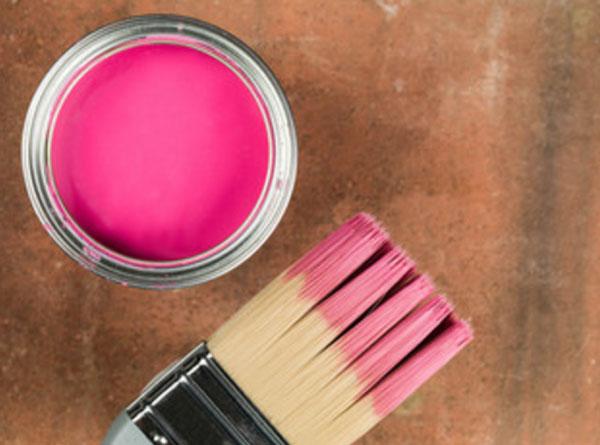 Банка с розовой краской и кисточка, испачканная в ней