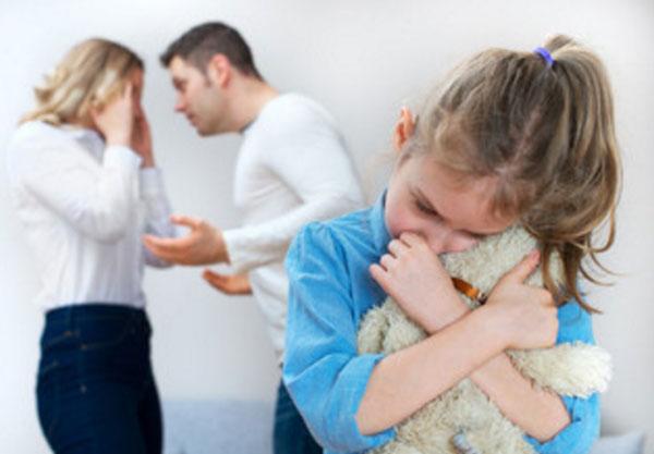 Девочка прижимается к мягкой игрушке. На заднем плане ее родители ругаются