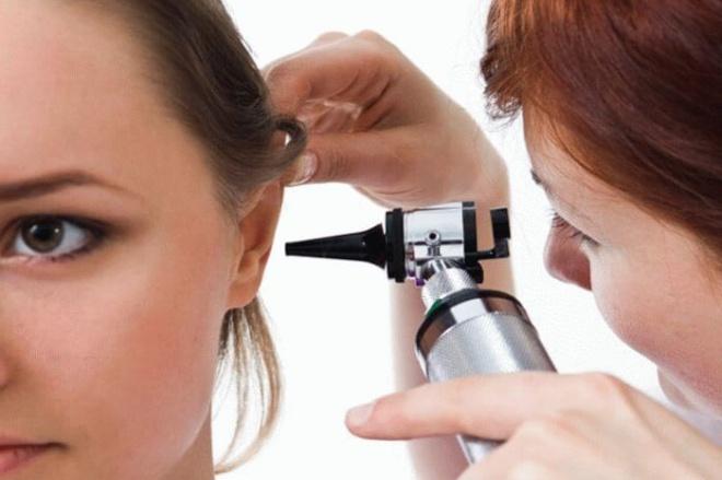 врач проверяет ухо