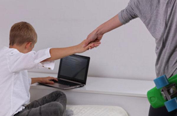 Мальчика возле ноутбука пытается оттянуть парень со скейтом в руке