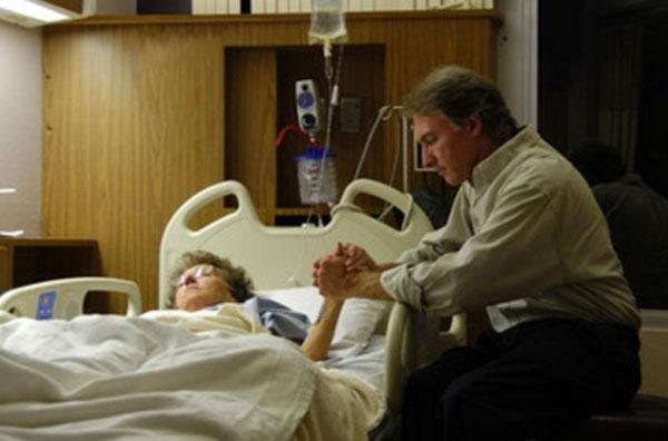 Мужчина сидит у кровати женщины, которая лежит под капельницей