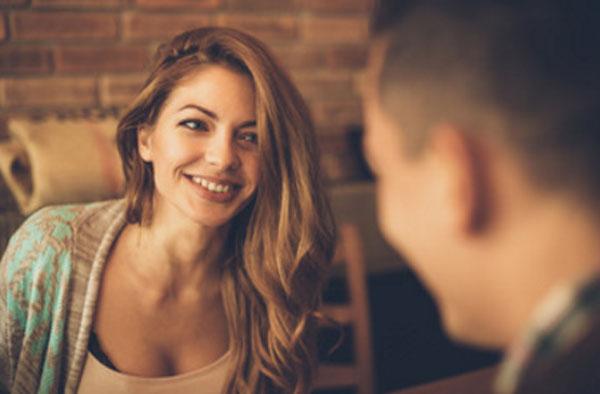 Парень с девушкой общаются в кафе. Девушка смотрит на него с восхищением