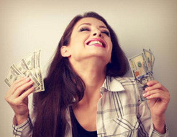 Девушка счастлива, держит деньги в обеих руках