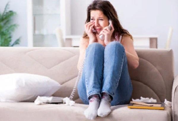 Женщина сидит на диване с трубкой в руке и плачет
