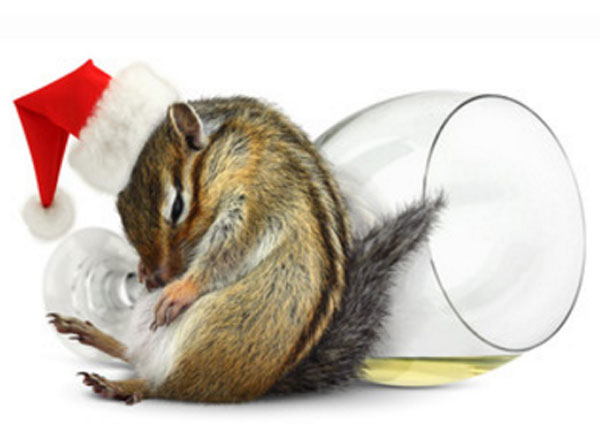 Белочка в новогодней шапочке спит рядом с перевернутым бокалом. В нем остатки спиртного