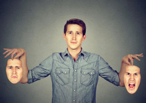 Мужчина с нормальным выражением лица держит в руках два своих лица, депрессивное и агрессивное