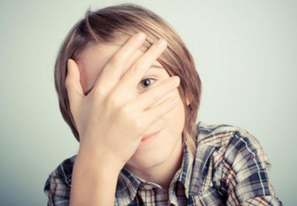 Мальчик прячет свое лицо рукой