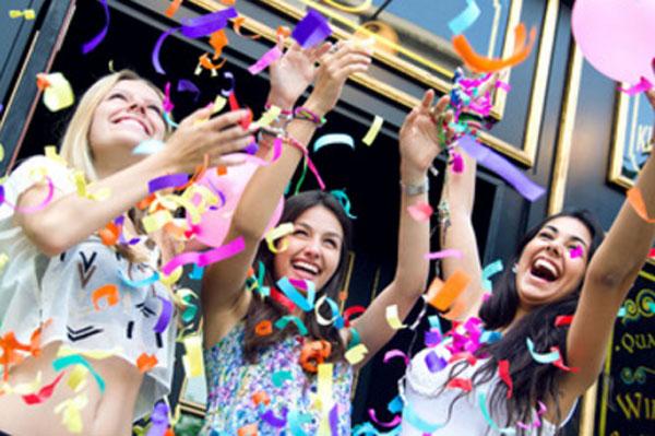 Девушки улыбаются и смеются, у них шарики и летает конфети