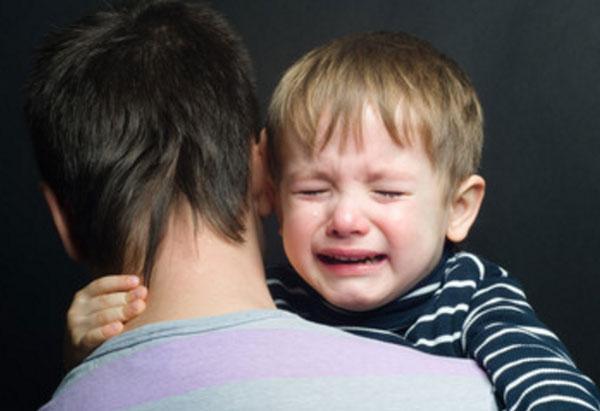 Ребенок плачет на руках у папы