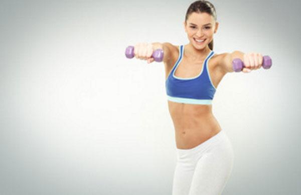 Девушка в спортивной форме с гантелями в руках