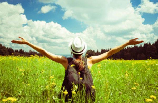 Девушка сидит на траве, поднимая руки к солнцу