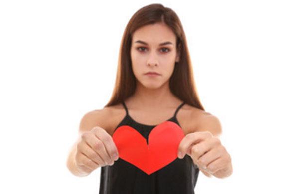 Серьезная девушка рвет картонное сердце