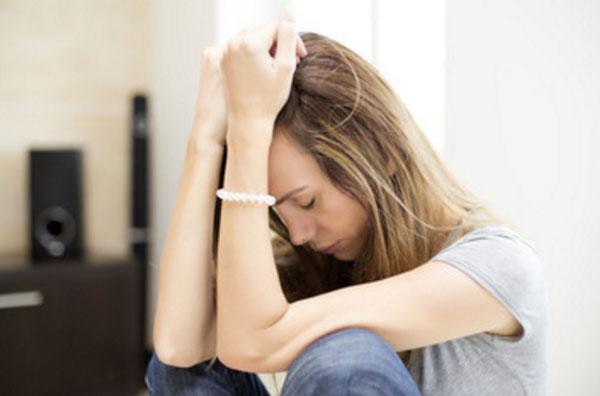 Огорченная девушка сидит на полу