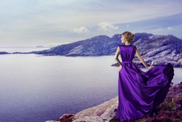 Женщина в фиолетовом платье стоит на берегу