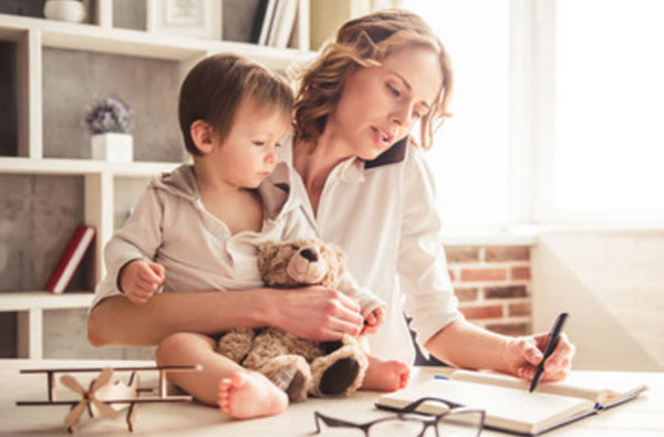 Женщина одновременно сидит с ребенком и занимается работой