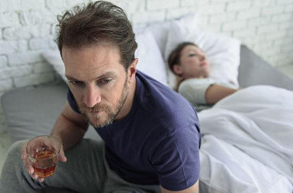 Плохо выглядевший мужчина сидит на краю кровати со стаканом спиртного в руке