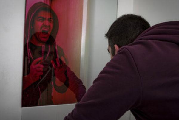 Мужчина смотрит в зеркало и видит в нем себя, желающего покончить с жизнью