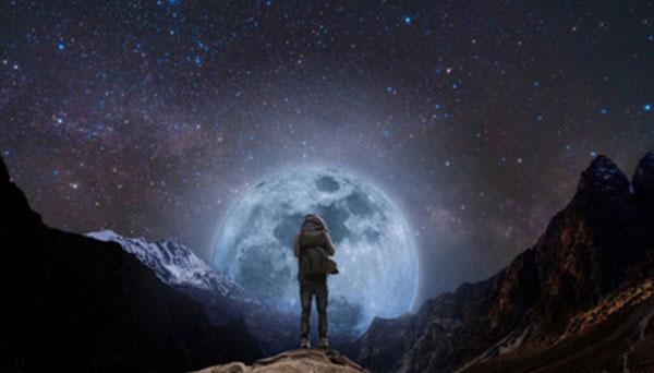 Человек стоит на возвышенности. Перед ним огромная луна