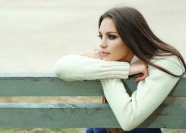 Грустная девушка сидит на скамейке
