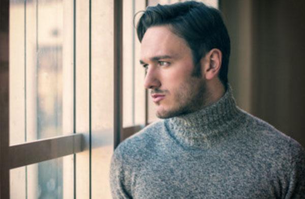 Красивый мужчина смотрит в окно