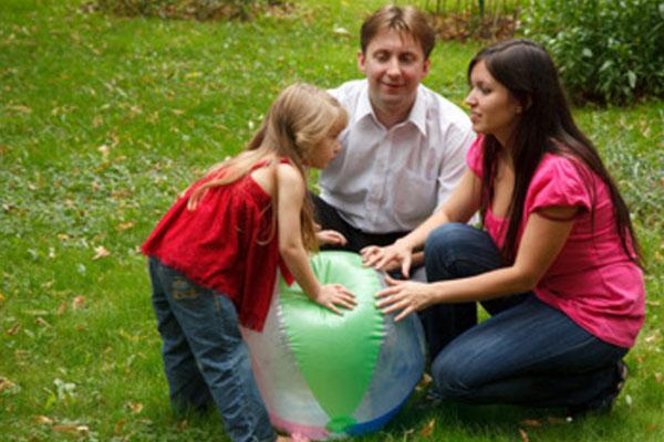 Девочка играет надувным мячом вместе с папой и мамой