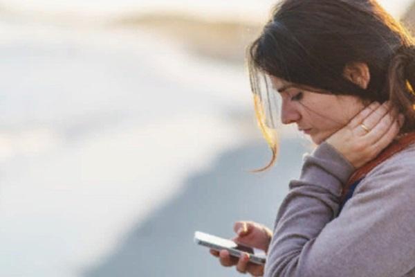 Грустная женщина смотрит в телефон