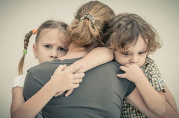 Мама обнимает дочку и сына, которые к ней прижимаются