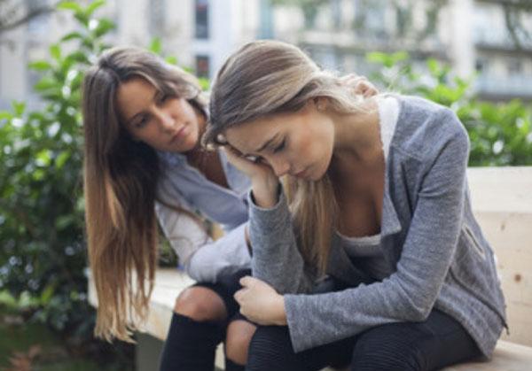 Расстроенная женщина. Вторая девушка оказывает поддержку