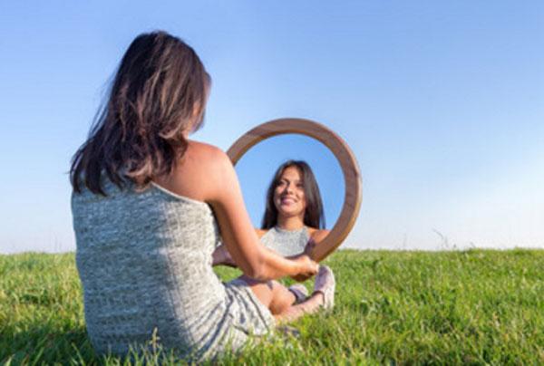 Девушка сидит на траве. у нее в руках круглое зеркало, в которое она смотрит