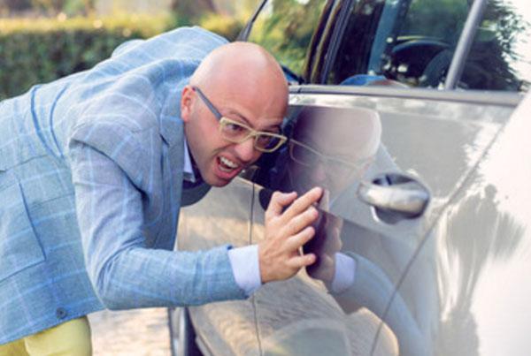 Мужчина проверяет, чтоб на машине не было ни царапинки