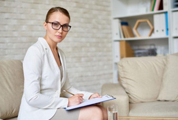Психотерапевт в очках, с планшетником и ручкой в руках