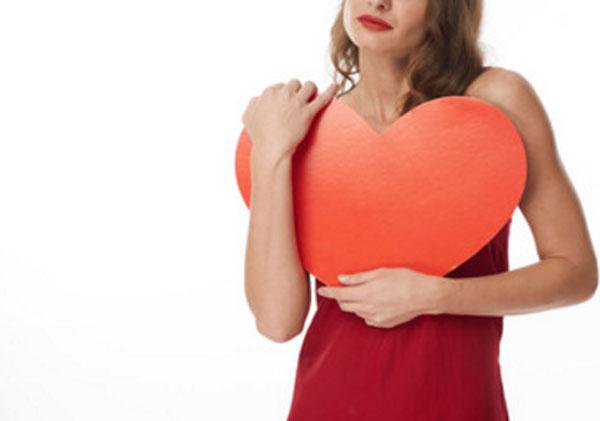 Девушка держит в руках большое картонное сердце. Ее лица не видно на снимке