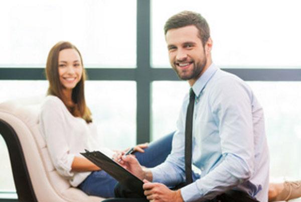 Счастливая женщина на приеме у улыбающегося психотерапевта