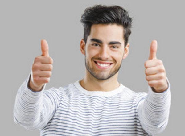 Молодой улыбающийся мужчина поднимает оба больших пальца вверх