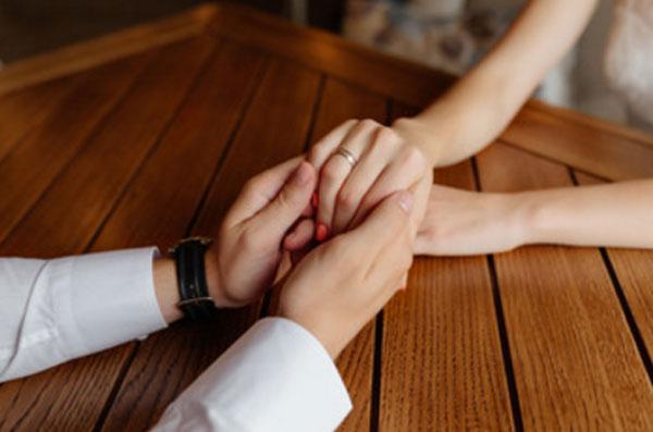 Мужские руки держат женскую. На безымянном пальце кольцо