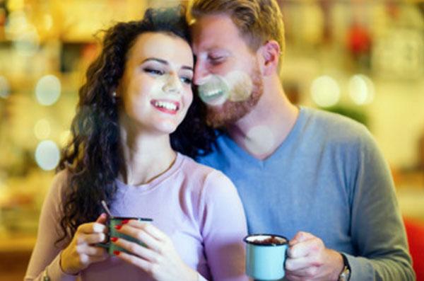 Счастливые парень с девушкой с чашками в руках