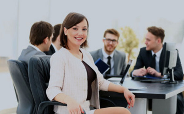 Харизматичная женщина сидит за столом с мужчинами