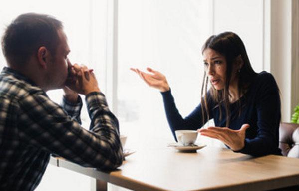 Женщина разговаривает с мужем за столиком в кафе