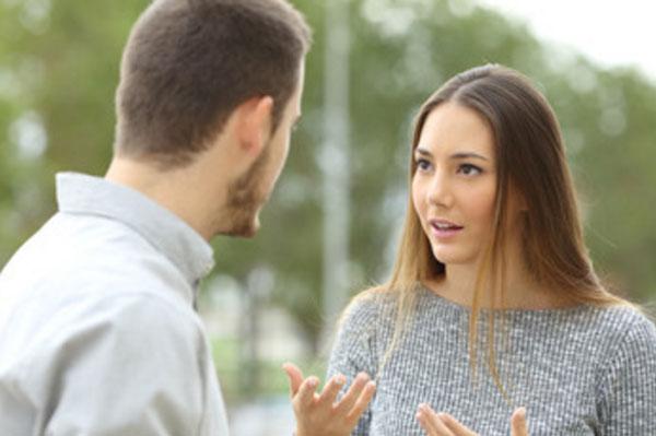 Парень стоит лицом к девушке, она что-то пытается ему объяснить