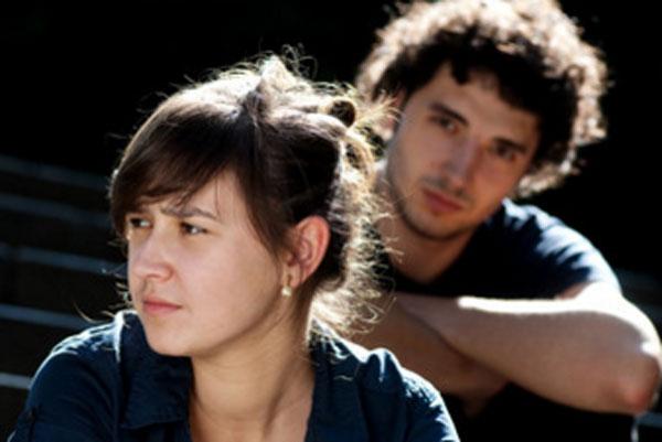 Девушка сидит впереди парня и смотрит в сторону.