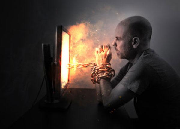 Мужчина сидит перед экраном монитора. Его руки скованы цепью