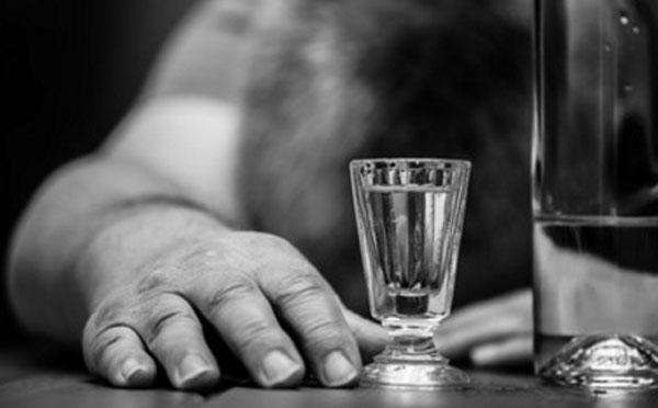 Мужчина лежит лицом на столе. Перед ним почти выпитая бутылка водки и рюмка