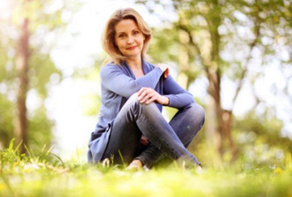 Счастливая женщина сидит на траве